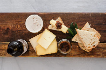 birds eye view of a cheese board with a beer