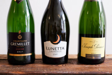 three bottles of sparkling wine on a wooden table