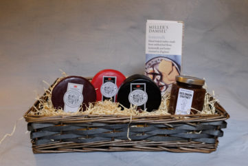 a gift basket containing cheeses chutney and crackers