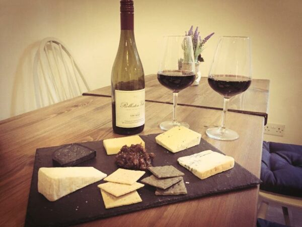 a selection of cheeses and a bottle of wine