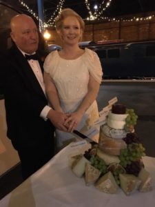a couple stand next to their cheese cake tower
