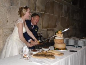 couple use sword to cut cheese cake tower at wedding