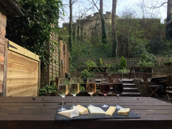 5 cheese and wine pairings on a table in the garden