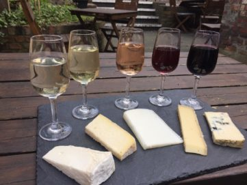 5 wine and cheese pairings on a black slate